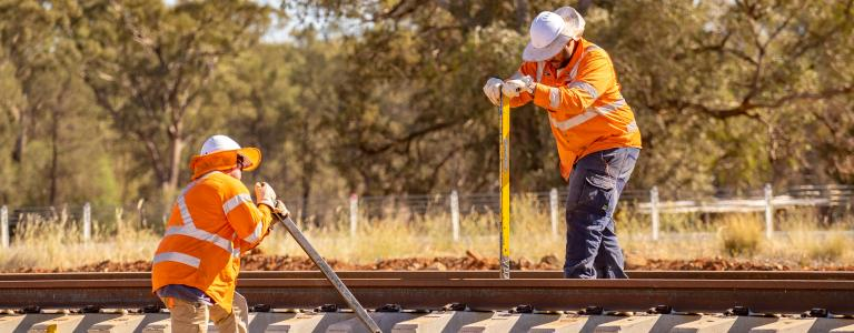 Two construction workers wearing orange high vis clothing installing rail