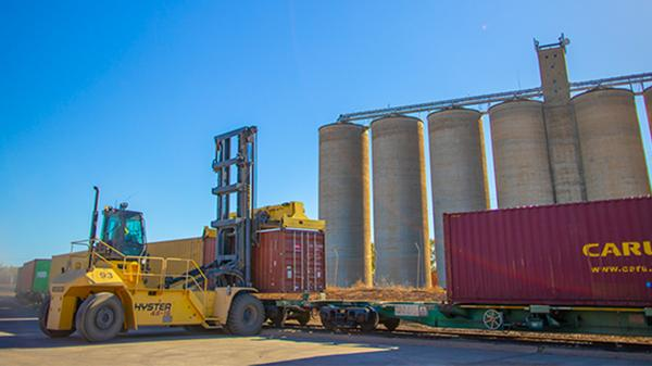 Freight train with loading and unloading machinery in front of a grain storage facility